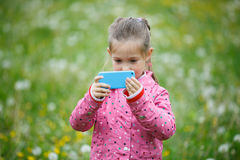 Little girl photographing with her smart phone Royalty Free Stock Photography