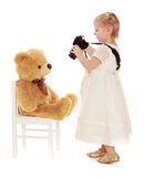 Little girl photographs on the camera teddy bear Royalty Free Stock Photo
