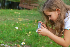 The little girl photographs a flower. The little girl with the old camera in a white dress Royalty Free Stock Images
