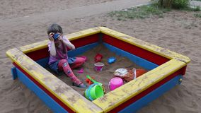 Little girl photographs by toy camera in sandbox stock video