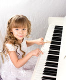 Little girl and piano. Little beautiful girl with blond long curls in white feshion dress playing on white piano Stock Photography