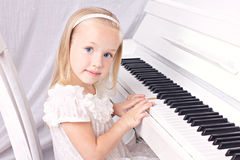 Little girl at piano. Little beauy blond girl in white beautiful dress  sitting at white piano, looking at camera Royalty Free Stock Photos