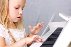 Little girl at piano. Little blond girl in beautiful white dress plaing on white piano, closeup Royalty Free Stock Photo