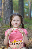 Little girl pick up mushrooms in forest Stock Photo