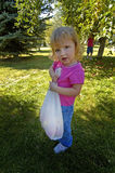 Little Girl Picking Apples. And holding sack of apples Royalty Free Stock Photography