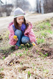Little girl picking bunch of small yellow flowers Stock Images