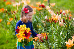 Little girl picking lilly flowers Stock Photo
