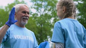 Little girl picking litter in park, giving high-five to grandfather, eco project. Stock footage stock footage