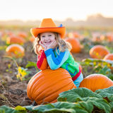 Child playing on pumpkin patch. Little girl picking pumpkins on Halloween pumpkin patch. Child playing in field of squash. Kids pick ripe vegetables on a farm in Stock Images