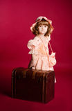 Little girl picking up a wooden trunk Royalty Free Stock Photos