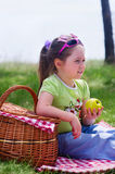 Little girl with picnic basket and apple Stock Photo
