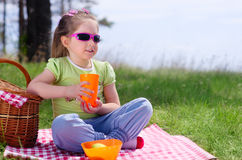 Little girl with picnic basket and plastic cup Royalty Free Stock Photo
