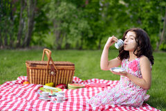 Little girl picnic drinking tea Royalty Free Stock Photography