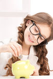 Little girl with piggy bank and coin Stock Photography