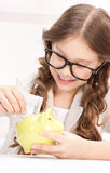 Little girl with piggy bank and money Stock Photo