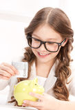 Little girl with piggy bank and money Royalty Free Stock Photos