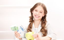 Little girl with piggy bank and money Stock Photography