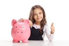 Little girl with a piggybank sitting at a table and making a thu. Mb up gesture isolated on white background Stock Photo