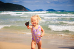 Little Girl with Pigtail Shows Shell Smiles by Foamy Waves. European cute little blond girl in swimsuit with pigtail shows nice shell smiles by foamy wave surf Royalty Free Stock Image