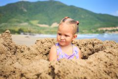 Little Girl with Pigtail in Swimsuit Sits on Sand Beach Royalty Free Stock Photography