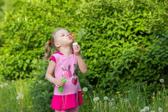 Little girl with pigtails blows soap bubbles Royalty Free Stock Photo