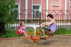 Little girl with pigtails and dad spins on carousel Stock Photos
