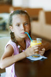 Little girl with pigtails drinking Royalty Free Stock Image