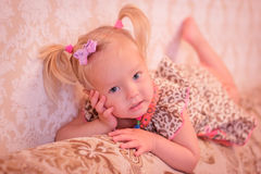 Little girl with pigtails lies Stock Photo