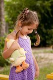 Little girl with pigtails nursing toy. Stock Images