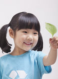 Little girl with pigtails in recycling symbol t-shirt looking at leaf, close up studio shot Royalty Free Stock Photography