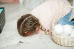 Little girl with pigtails is sitting on the floor, her face buried in a fluffy white carpet. Stock Image