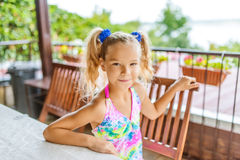 Little girl with pigtails sitting in gazebo Stock Images