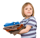 Little girl with a pile of T-shirts Royalty Free Stock Photography