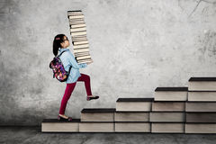 Little girl with pile of textbooks Stock Photo