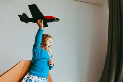Little girl with pilot glasses and wings play fly at home. Kids play home Royalty Free Stock Image