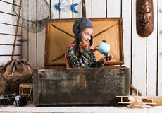 Little girl-pilot in wooden chest watching globe Royalty Free Stock Image