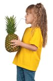 Little girl with pineapple Stock Images