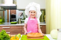 Little girl in pink apron cutting bread. Royalty Free Stock Photos