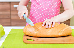 Little girl in pink apron cutting bread. Stock Photography