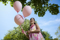 Little girl with pink balllons Stock Images