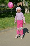 Little girl with pink balloon riding on roller blades. Along the steet Stock Image
