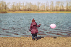 Little girl with a pink balloon on riverbank Royalty Free Stock Photos
