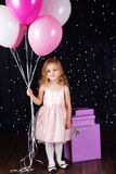 Little girl with pink balloons and gift boxes Royalty Free Stock Images