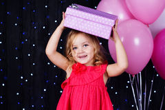 Little girl with pink balloons and gift boxes Royalty Free Stock Photo