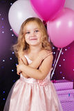 Little girl with pink balloons and gift boxes Stock Images