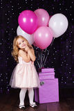 Little girl with pink balloons and gift boxes Stock Photography