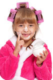 Little girl in pink bathrobe with curlers and cream Stock Photo