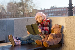 Little girl in a pink beret sits. On a bench in sunny autumn day with the book and a toy bear Stock Images