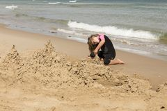 Little girl in pink and black wetsuit making sand castles. At the beach, Magdalen Islands, Quebec, Canada Royalty Free Stock Images