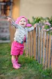Little girl in pink boots near the fence Royalty Free Stock Photos